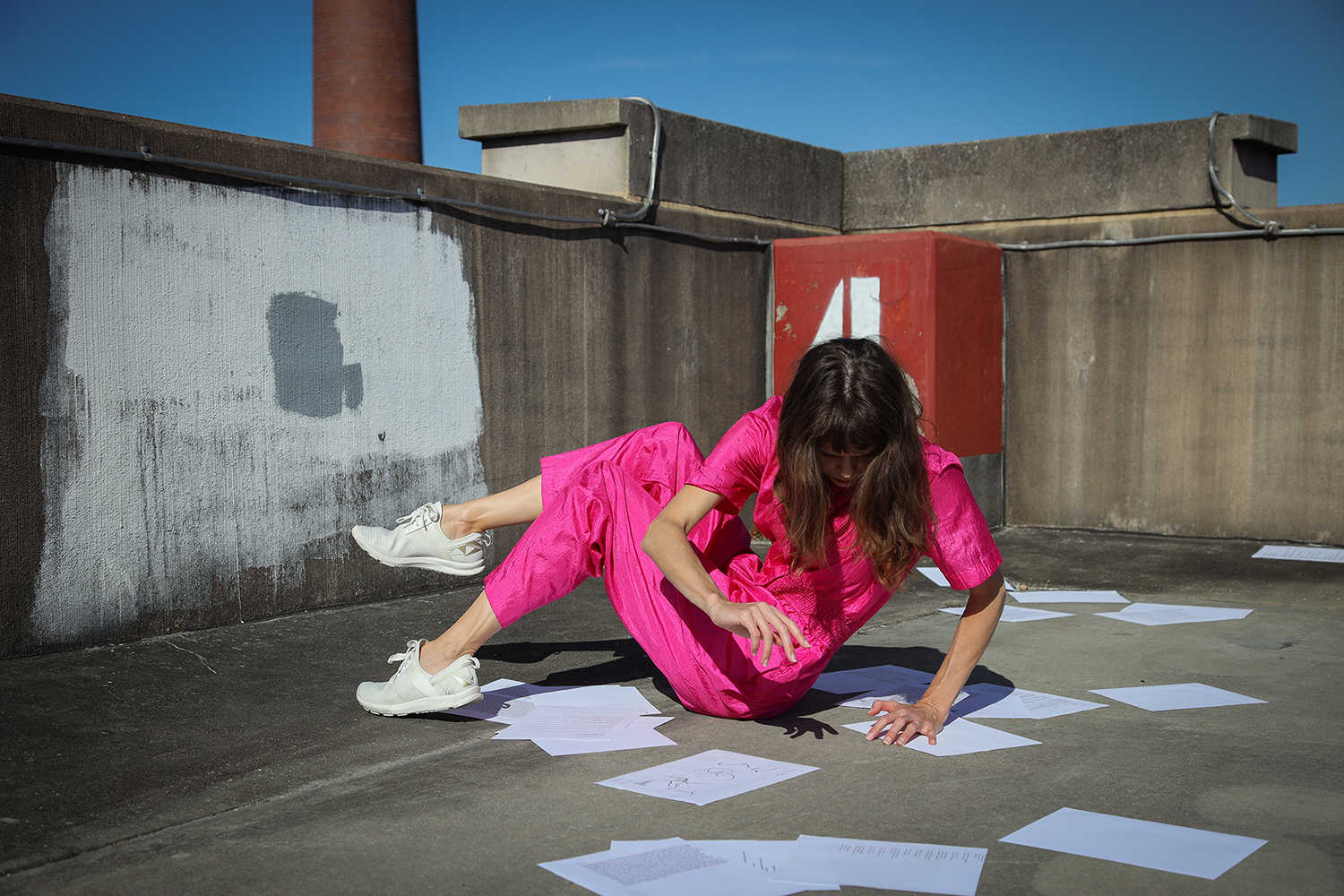 Person with long brown hair, wearing a pink jumpsuit and white sneakers, sustains a position in the corner of a concrete parking garage with papers strewn about.