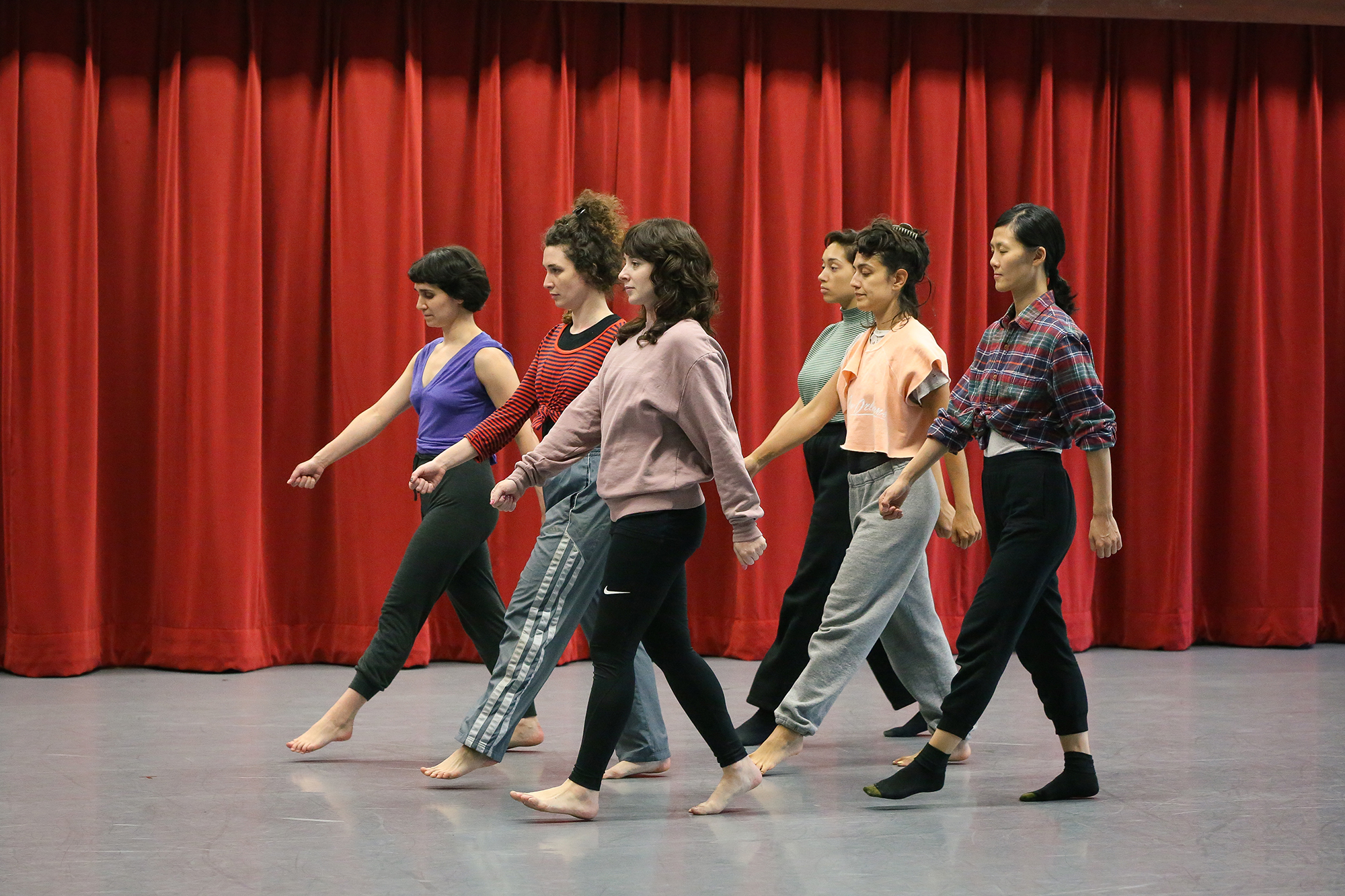 Six casually dressed people walk in unison in a two-line formation in front of a red curtain on a grey floor.